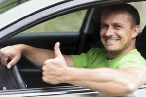 Guy with thumbs up driving a car he Novated Lease Company - How to Choose a good one